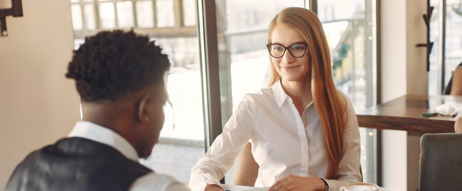 a woman sitting on a table interviewing a man