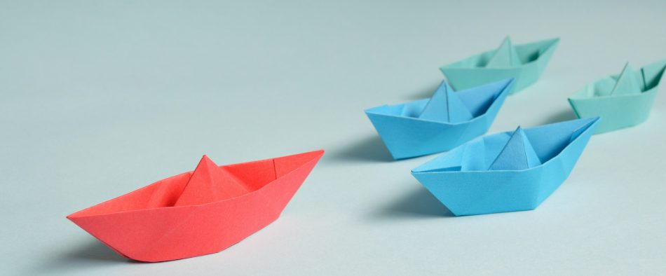 red paperboat leading other paperboats